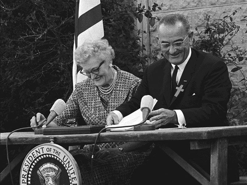 President Lyndon B. Johnson signs the ESEA in 1965 with Kate Deadrich Loney, his first schoolteacher.