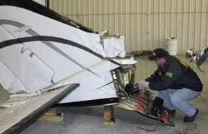 In this April 8 photo provided by the National Transportation Safety Board, air safety investigator Todd Fox examines the tail section of the Cessna 414A twin-engine aircraft that April 7.