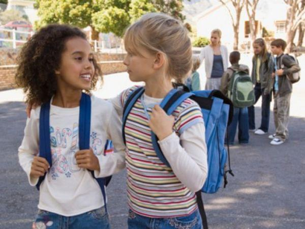 Two young girls with school backpacks look at each other as they walk ahead of a group of classmates