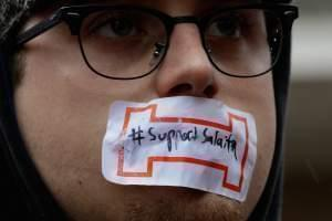 """Protester with a sideways """"I"""" over his mouth. The sideways """"I"""" represents censorship imposed by the university and the lack of academic freedom."""