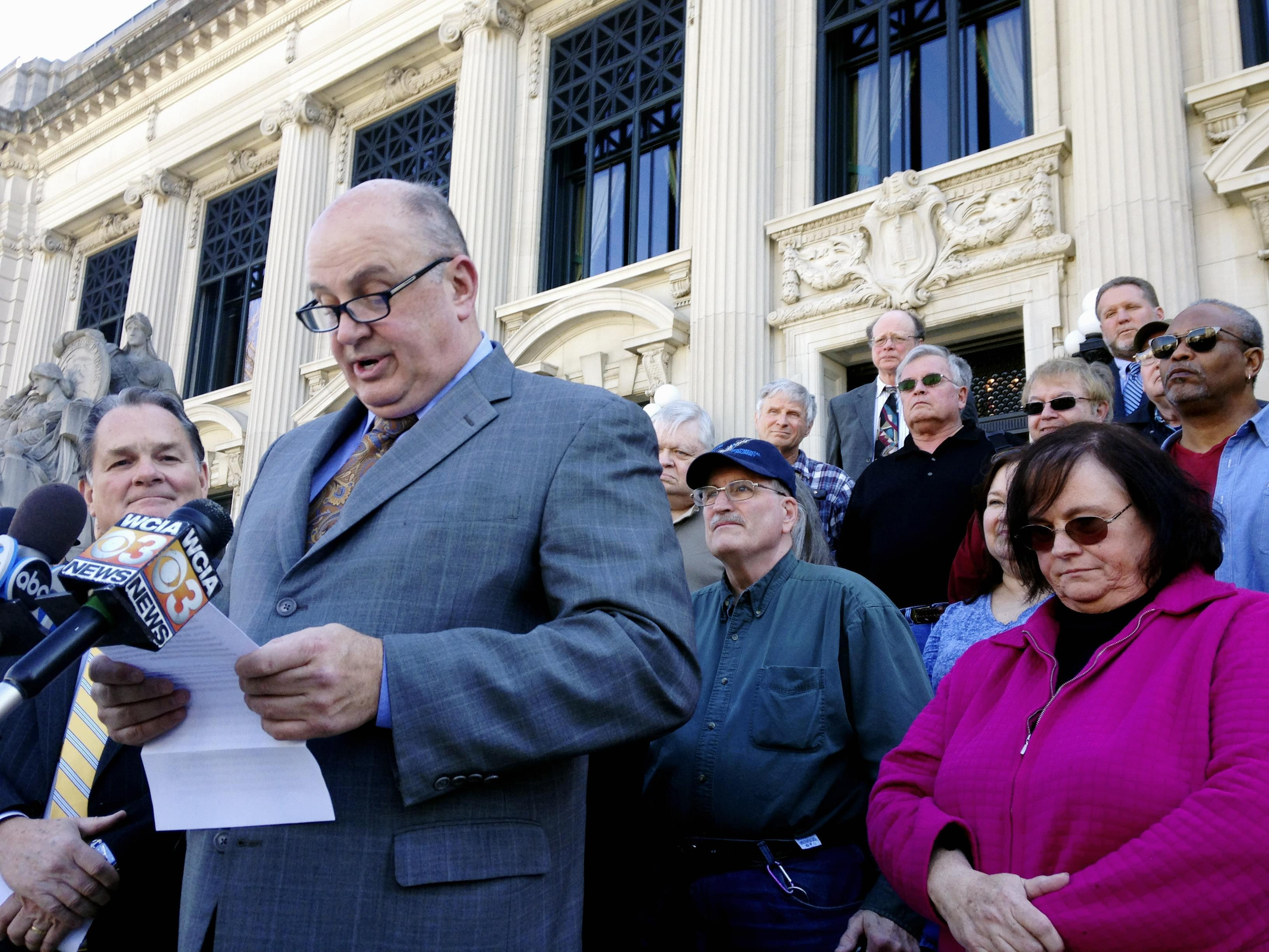 Illinois AFL-CIO President Michael Carrigan is joined by state workers and retirees outside the Illinois Supreme Court in Springfield, Ill., Wednesday, March 11, 2015, as he addresses the media following oral arguments in a lawsuit over a state pensi