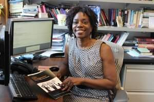 Researcher Ruby Mendenhall sits in her office holding a copy of the Racial Microaggressions in the Classroom report.