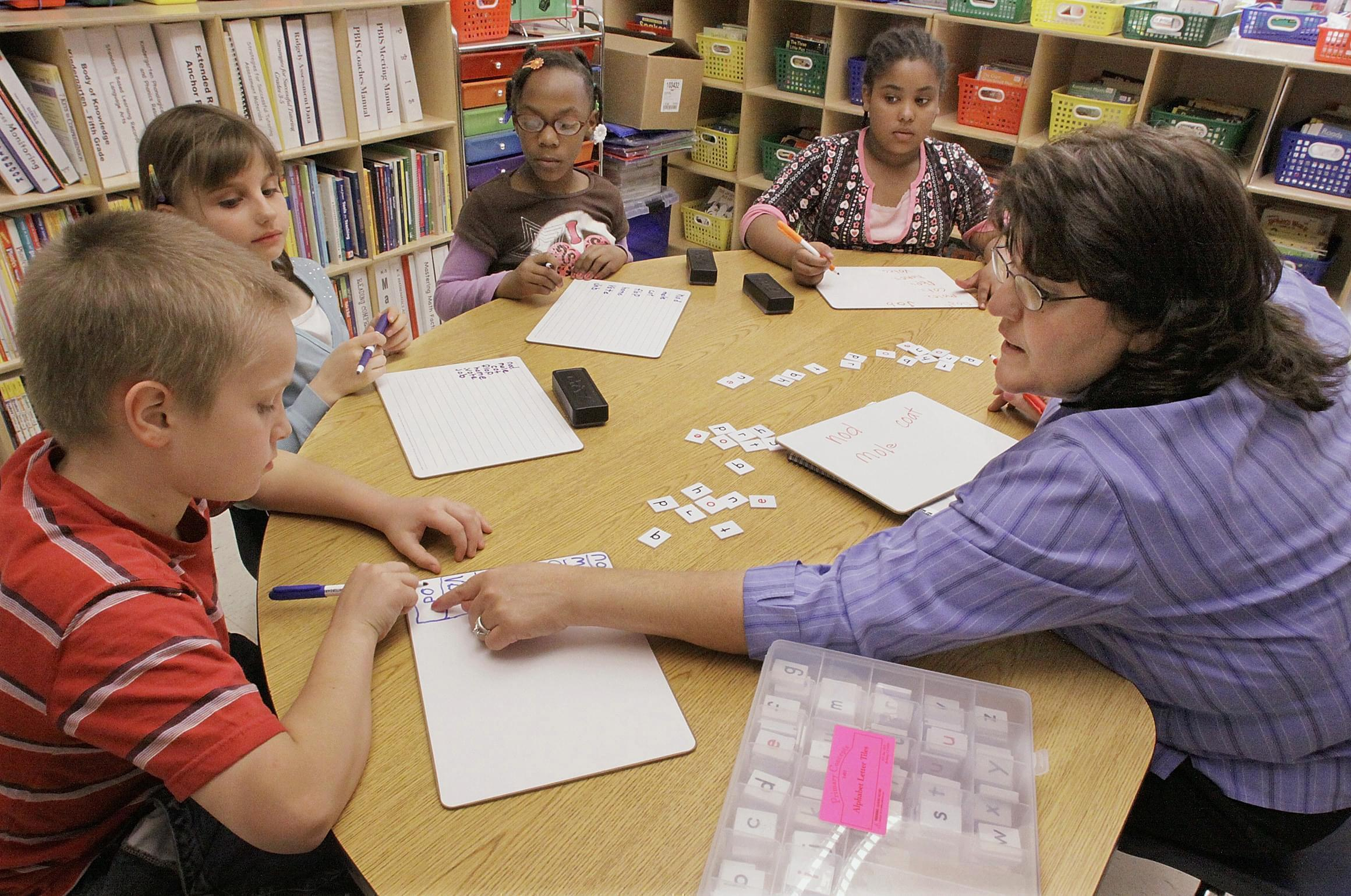 Jackie Peters, right, works with her third grade students at Ridgely Elementary School in Springfield, Ill. Over two years, Illinois will get about $1 billion in federal grants such as special education and Title I, which provides grants for low-inco