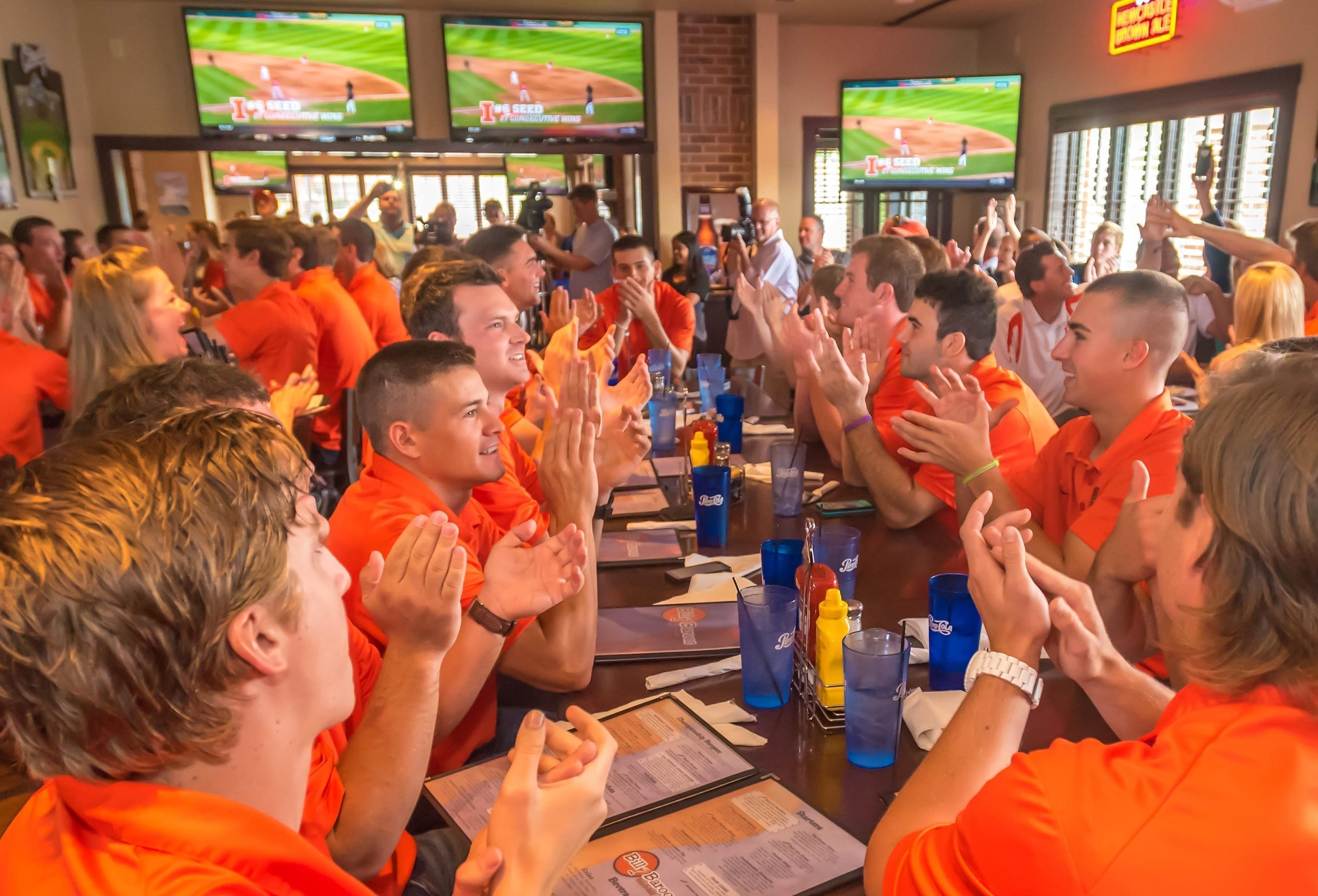 Members of the Illinois baseball team cheer as they learn about their No. 6 national seed in the NCAA Baseball Tournament at Billy Barooz in Champaign Monday.
