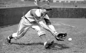In this April 29, 1942, file photo, Chicago Cubs' Lennie Merullo fields a baseball in Chicago. The oldest former member of the Cubs and the last living person to play for them in the World Series, he died Saturday at age 98.