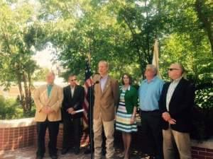 Gov. Bruce Rauner stands next to Senate Republican Leader Christine Radogno and others decrying property taxes during a press conference in the governor's mansion gardens.