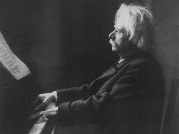 Elder composer at a piano.