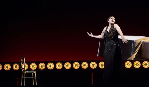 A woman rising from a couch on a stage during an opera