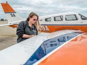 Bobbie Britz, who earned her flight instructor from the Institute of Aviation in 2014, goes through pre-flight equipment checks Tuesday.