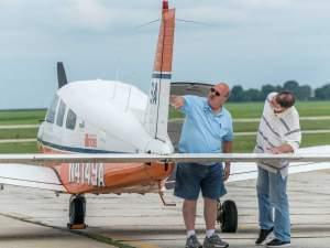 Two men inspecting the tail of an airplane