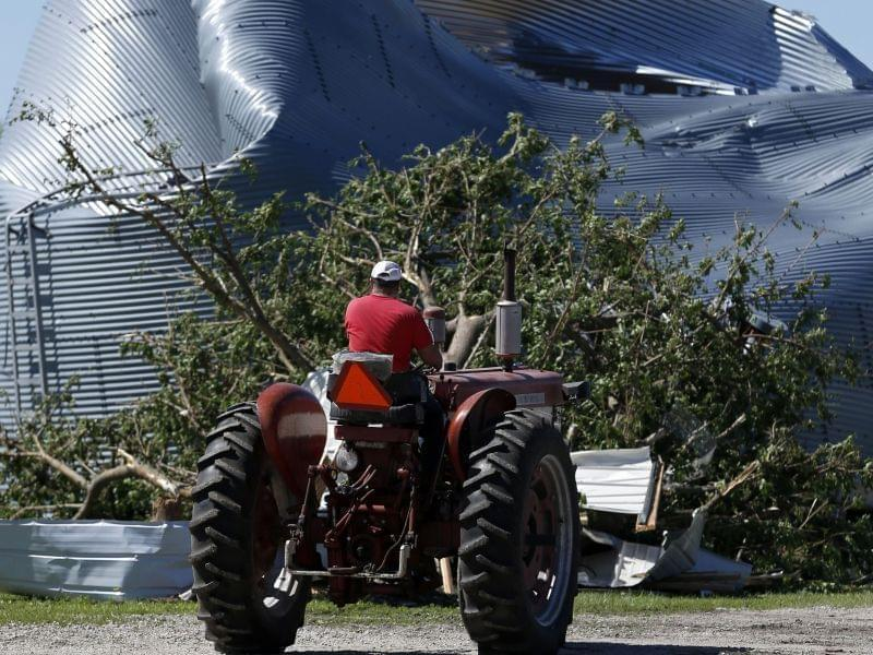 Bernie Burla drives a tractor past a damaged grain silo on his family farm Tuesday, June 23, 2015, in Coal City, Ill., after a tornado passed through the area Monday evening.