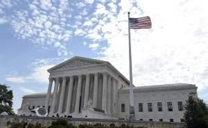 The flag flies in the wind in front of the Supreme Court in Washington, Monday, June 22.
