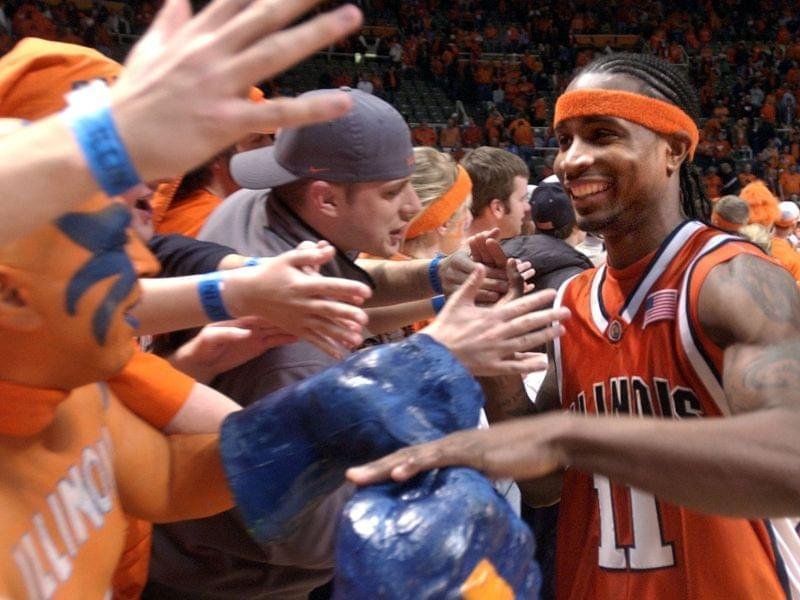 Illinois' Dee Brown slaps hands with members of the Orange Krush after Illinois beat Iowa 71-59 at the Assembly Hall in Champaign on Saturday Feb. 25, 2006.
