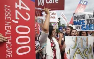 "Jessica Ellis, right, with ""yay 4 ACA"" sign, and other supporters of the Affordable Care Act, react with cheers as the opinion for health care is reported outside of the Supreme Court in Washington Thursday."