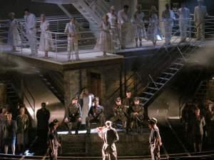 Stage scene from an opera with military and prisoner characters.