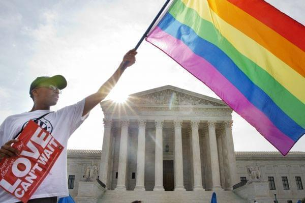 Carlos McKnight of Washington, waves a flag in support of gay marriage outside of the Supreme Court in Washington Friday.