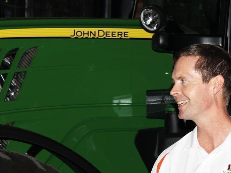 Illinois Congressman Rodney Davis stands alongside John Deere farm equipment during a tour of the AgReliant Genetics Champaign Research Station near Ivesdale.
