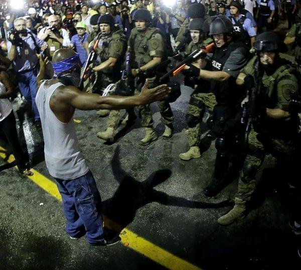 A black male is arrested by police during a protest following the shooting of unarmed, black teenager Michael Brown in Ferguson, MO.