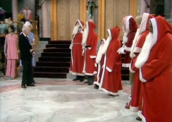 Young Mr. Grace inspects a line of people dressed as Santa.