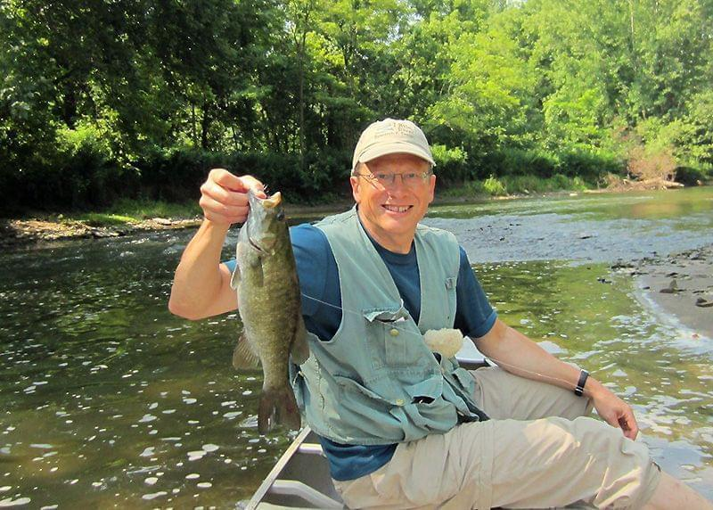 Rob Kanter holds a smallmouth bass in a boat on the Salt Fork River