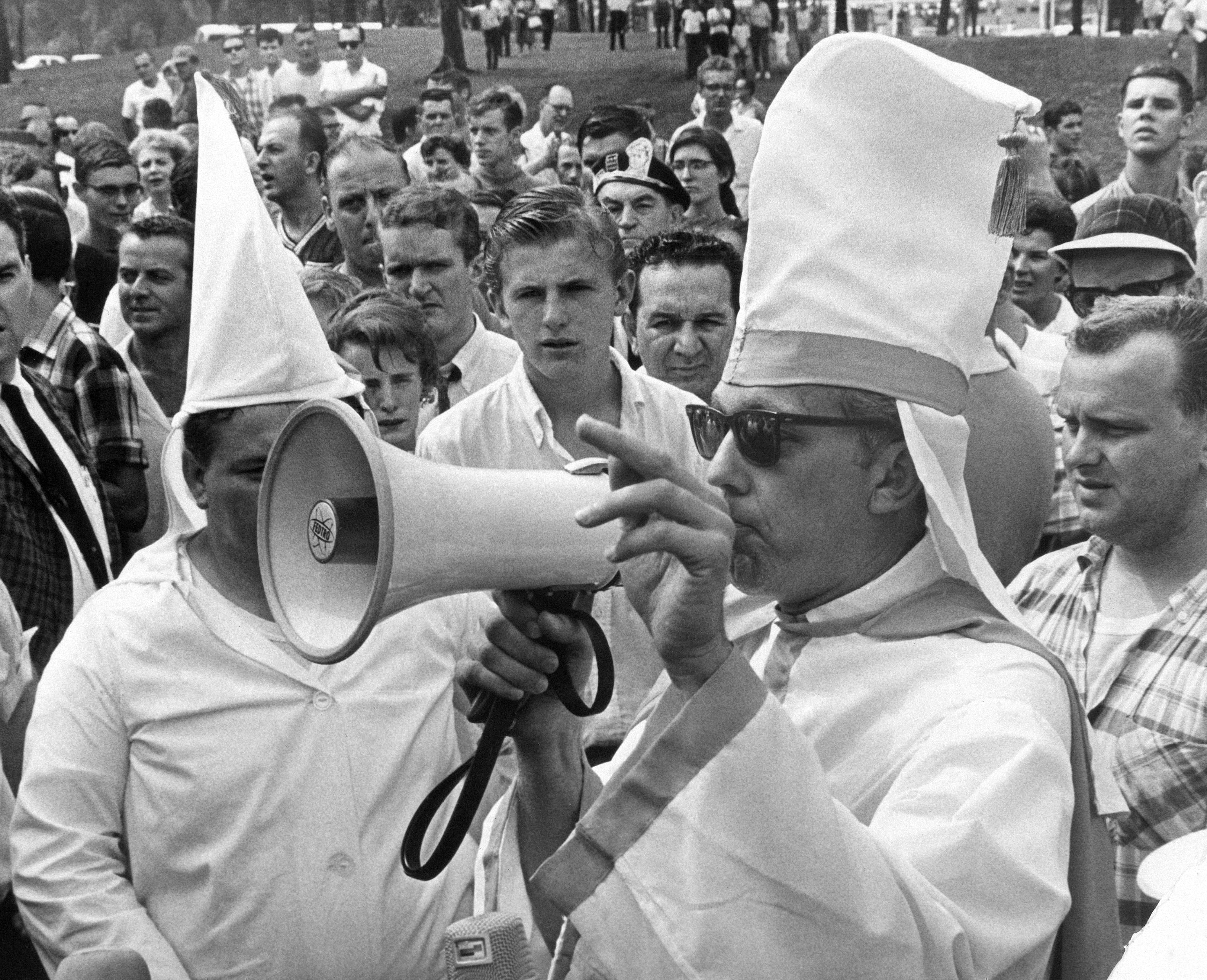 Man clad in Ku Klux Klan type robes uses bullhorn to address crowd in Marquette Park, Chicago on August 21, 1966 following rally staged by American Nazi Party. He was arrested for speaking without a permit and identified himself as Evan Lewis, 34, of