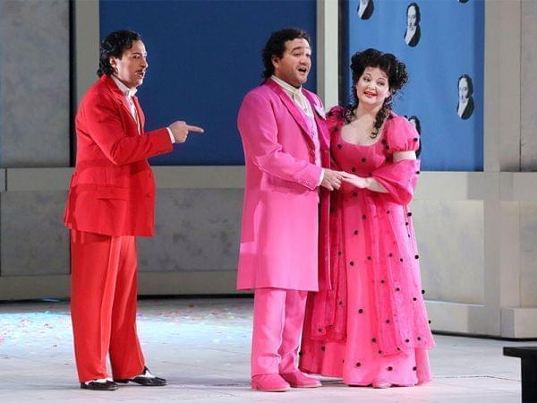 A stage scene from an opera with 2 men, 1 woman.