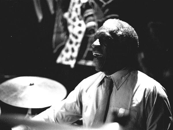 An African American man behind a drum set.