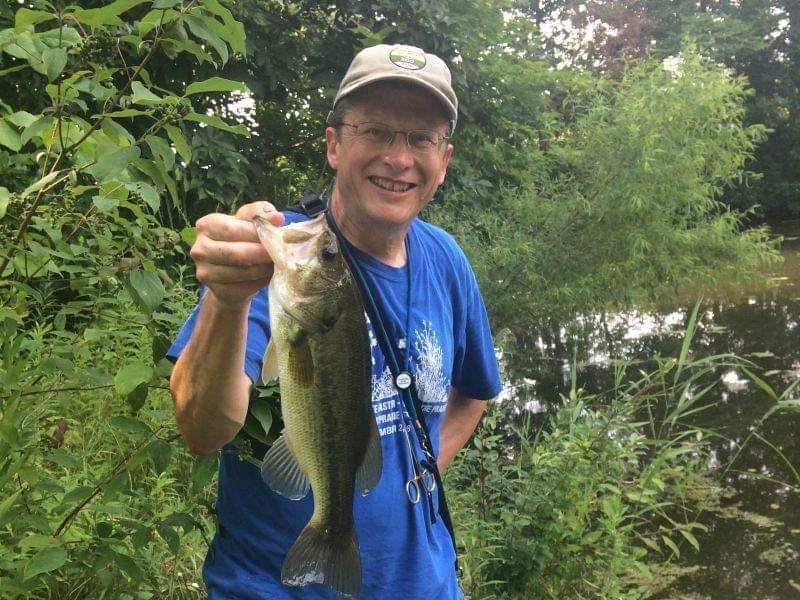 A close shot of the author displaying a forearm-length largemouth bass, with pond and bankside vegetation in the background.