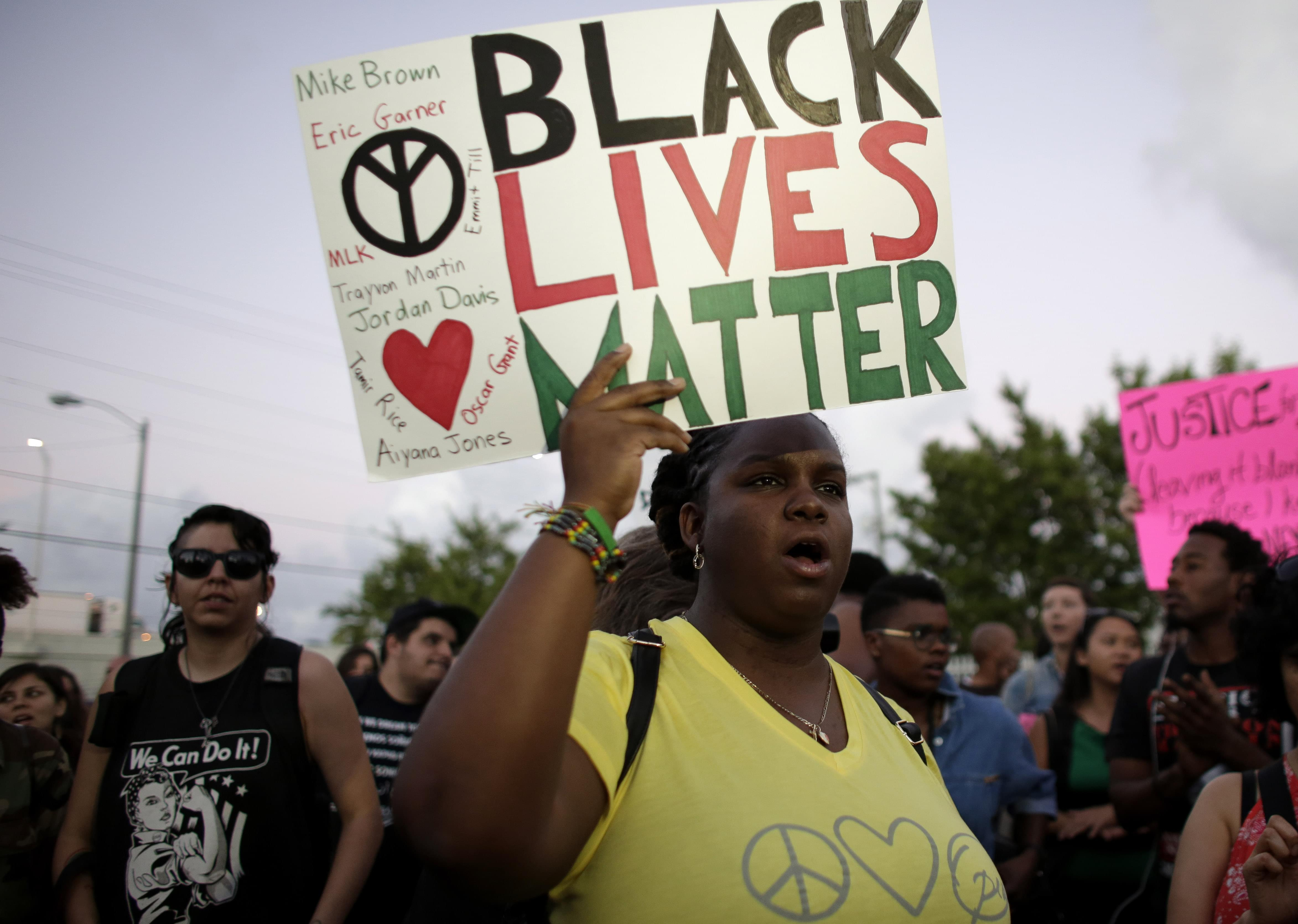 """Desiree Griffiths, 31, of Miami, holds up a sign saying """"Black Lives Matter"""", with the names of Michael Brown and Eric Garner, two black men recently killed by police, during a protest Friday, Dec. 5, 2014, in Miami. People are protesting n"""