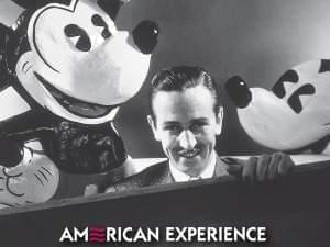 photo of Walt Disney with large Mickey Mouse figures behind him.