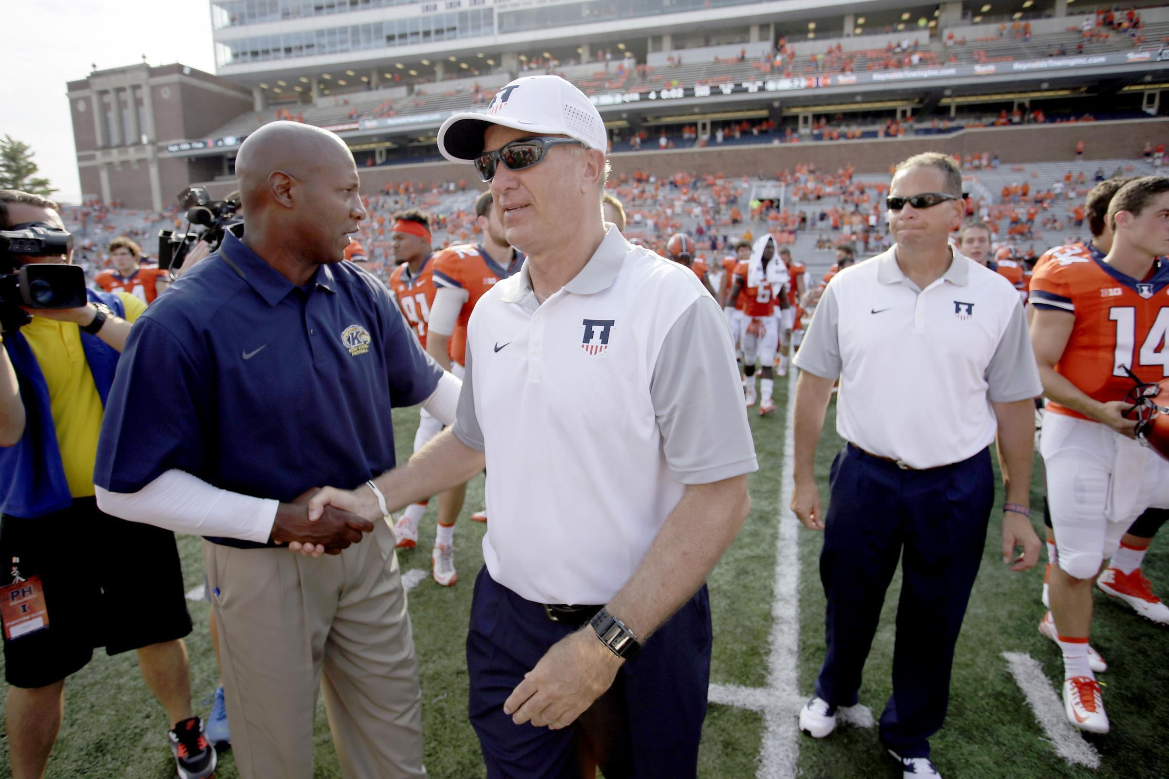 Illinois interim head coach Bill Cubit, right, shakes hands with Kent State head coach Paul Haynes at the end of Illinois' 52-3 victory Saturday in Champaign