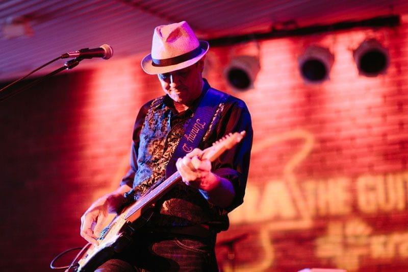 Tim Donaldson playing guitar on stage.