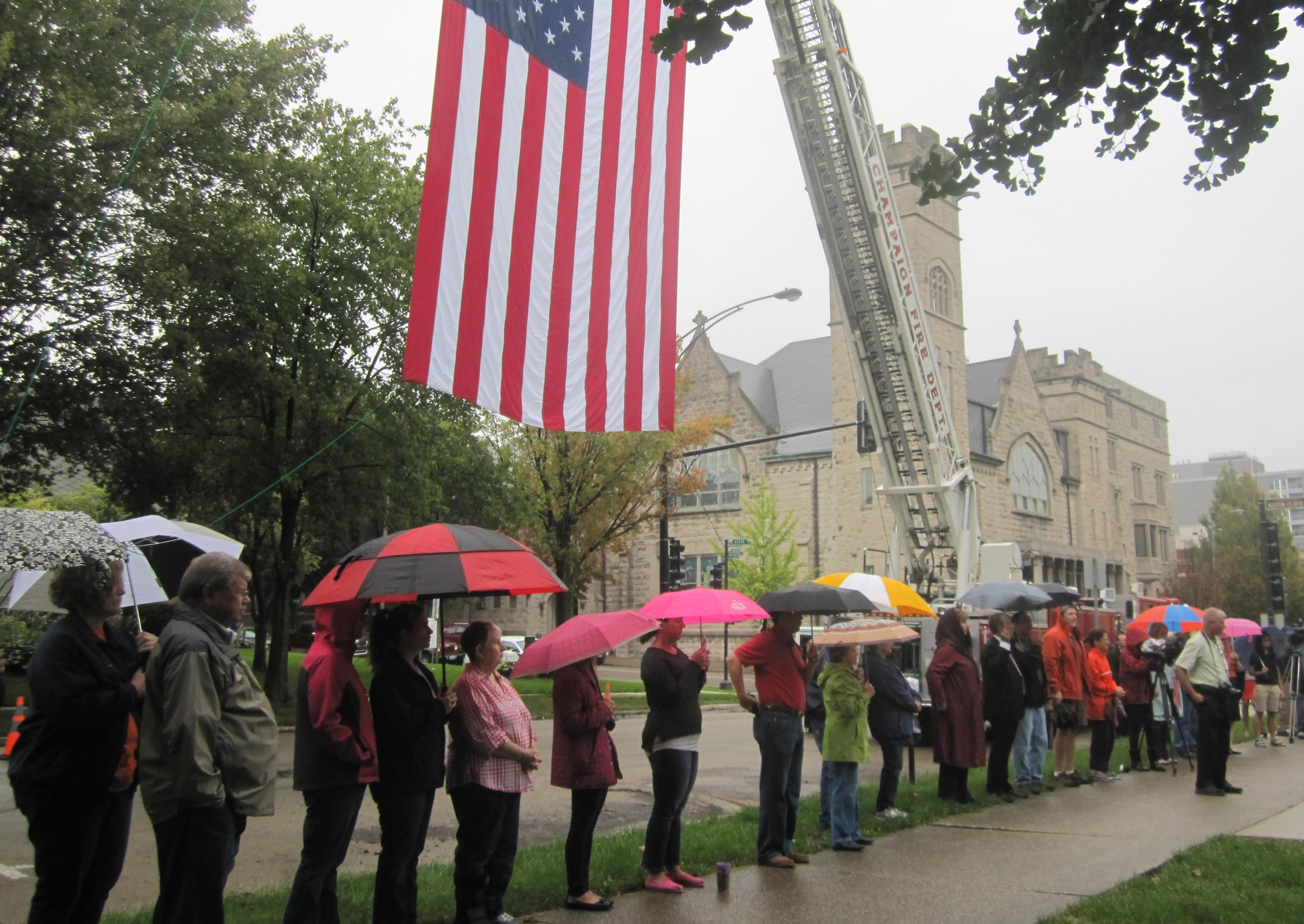 Onlookers with umbrellas gather for Champaign's 9-11 memorial ceremony at Westside Park, under a US flag hoisted by a crane.