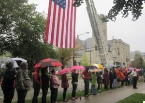 Onlookers with umbrellas gather for Champaign's 9-11 memorial ceremony at West Side Park in 2015, under a US flag hoisted by a crane.