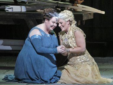 Two women comforting each other on stage