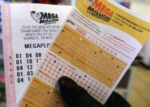 In this Dec. 12, 2013. file photo, a customer holds a Mega Millions lottery ticket at a convenience store in Chicago. State officials announced Friday, Aug. 15, 2014, that Illinois will end its contract with the private vendor that operates the $2 bi