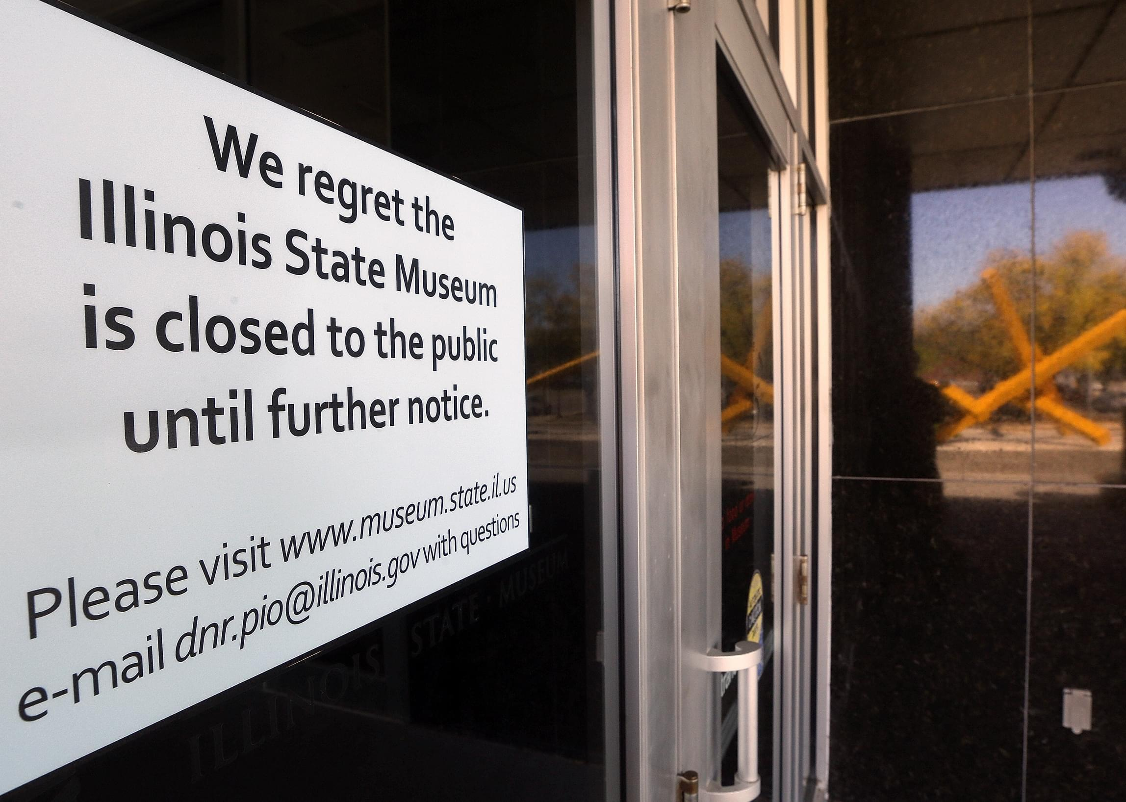 The reflection of a sculpture highlights the closing notice on the front door of the Illinois State Museum, Thursday, Oct. 1, 2015, in Springfield.