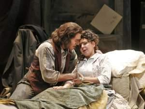 A man sits at the bed side of an ill woman, on stage