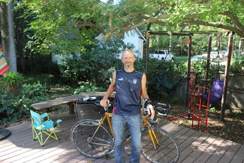 Ray Spooner standing with his bicycle outside his home in Urbana