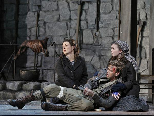 Injured man and two women on stage