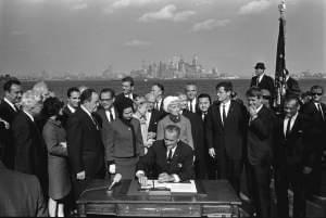 President Lyndon B. Johnson signs the 1965 Immigration and Nationality Act as Vice President Hubert Humphrey, Lady Bird Johnson, Muriel Humphrey, Sen. Edward (Ted) Kennedy, Sen. Robert F. Kennedy, and others look on.