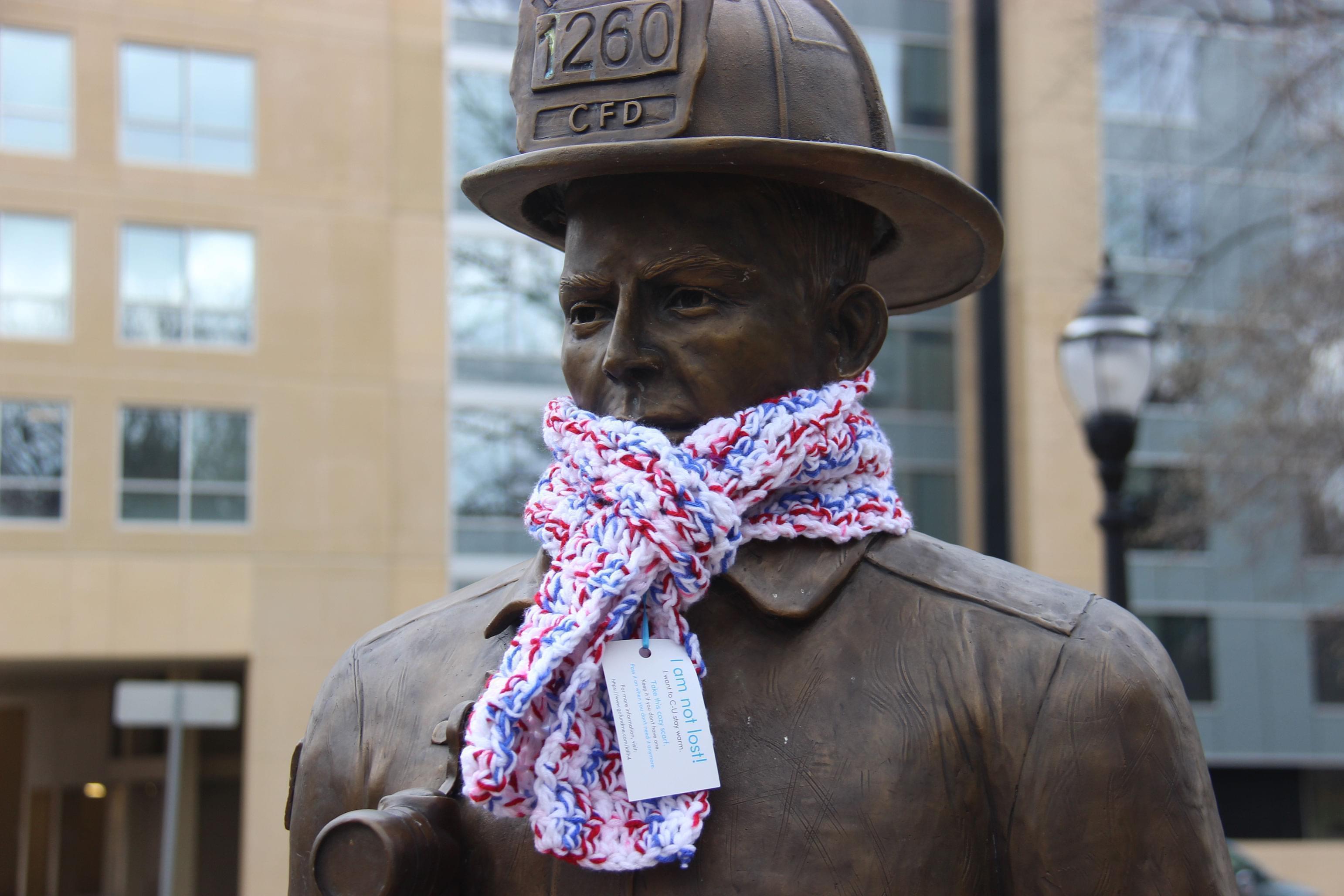 Fireman statue in West Side Park wearing one of Gretchen's scarves