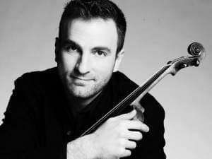A man posing with a violin