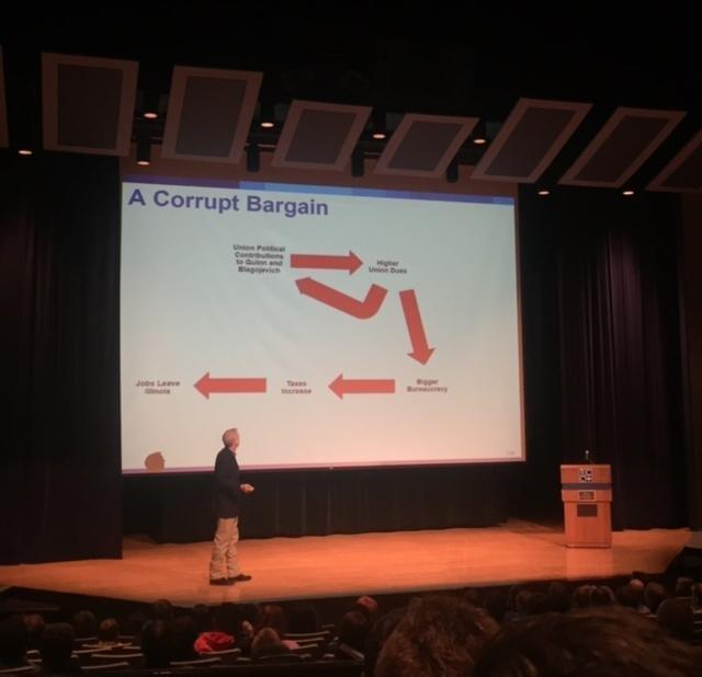 Gov. Bruce Rauner in front of an audience with a powerpoint presentation