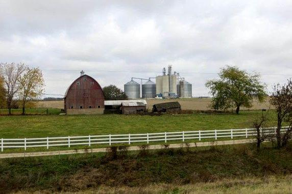 A barn, grain silos, pasture and crop land in a rural area.