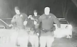 Still from police dashcam video of Benjamin Mann being led away by Champaign officers after altercation on March 16, 2014.
