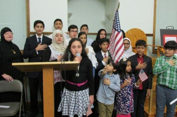 Muslim youth lead the pledge of allegiance and national anthem at the interfaith prayer vigil in Springfield