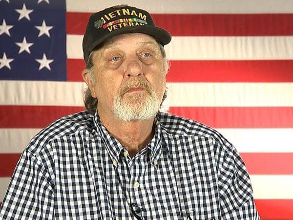 A man sitting in front of an American flag