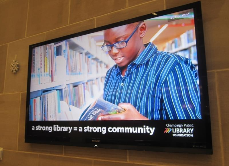 A monitor screen in the lobby of the Champaign Public Library displays an ad seeking donations for the Library Foundation.