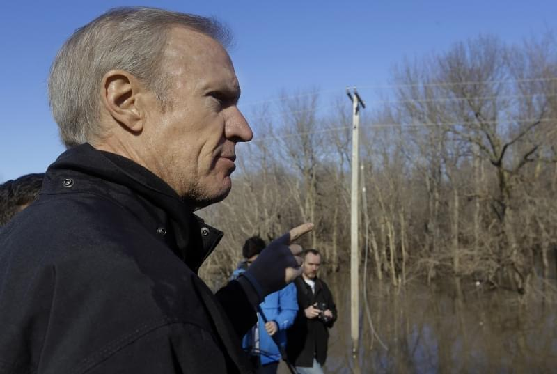 Illinois Gov. Bruce Rauner overlooks the south fork of the Sangamon River, where two teenagers were killed while crossing a flooded road last week, during his tour to the area Sunday in Kincaid, Ill